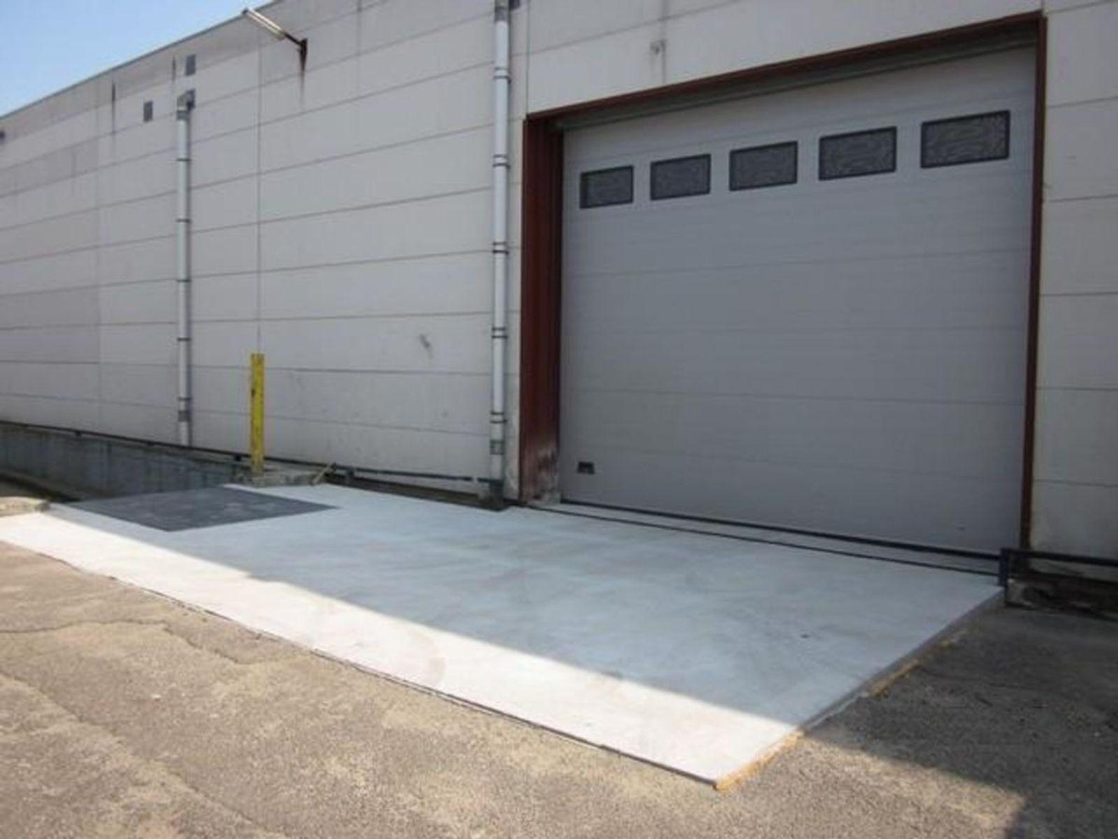Indeling-  Het complex is opgedeeld in meerdere afzonderlijke units waarvan thans een unit voor verhuur beschikbaar is. Deze unit omvat een bedrijfsruimte met inpandig kantoor en een toilet. Deze locatie is geschikt voor meerdere gebruiksfuncties.  Maatvoering- De bedrijfsruimte/opslagruimte kent een vloeroppervlakte van circa 2.450 m². Het buitenterrein met laad/los dock kent een vloeroppervlakte van circa 300 m².  Opleveringsniveau- De bedrijfsruimte is opgetrokken met betonplaten wanden en voorzien van een golfplaten dak.  De bedrijfsruimte is ondermeer voorzien van een betonnen vloer. Verder zijn er een alarm (inclusief meldkamercontact), brandblussers en haspels aanwezig. De ruimte is toegankelijk middels een drietal overheaddeuren met de afmetingen 5,350 m¹ x 4,525 m¹, 4,600 m¹ x 4,525 m¹ en 2,500 m¹ x 2,800 m¹.  Parkeren- Op aangesloten terrein is voldoende parkeergelegenheid aanwezig.  Bouw- Bedrijfsruimte- Bestaande bouw Bouwperiode- Omstreeks 1978  Overdracht- Huurprijs - Op aanvraag Status - Beschikbaar Aanvaarding - In overleg