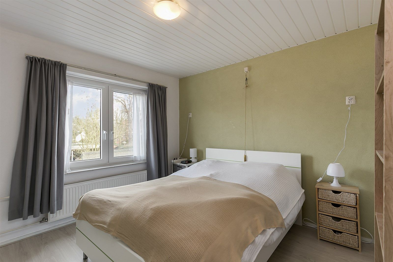 Deze middenwoning met vrijstaande berging is gelegen in een kindvriendelijke woonwijk aan een plantsoen met speelvoorziening. Op korte afstand bereik je naast alle dorpsvoorzieningen ook het unieke watergebied -De Warande-, omgeven door groen en wandelpaden. De A58 (Tilburg-Breda) is eveneens op korte afstand bereikbaar!   De woning is voorzien van kunststof kozijnen met dubbele beglazing en heeft een woonkamer met gaskachel en tuindeur naar de achtertuin, een keuken, drie slaapkamers, een praktische wasruimte, een moderne badkamer en een ruime bergzolder bereikbaar viaeen vlizotrap.   De voor- en achtertuin zijn beide verzorgd aangelegd waarbij de achtertuin tevens toegankelijk is via een achterom aan de achterzijde.    BEGANE GROND Entree/hal met toegang tot de toiletruimte, voorraadkast, woonkamer, keuken en vaste trap naar de  eerste verdieping. Afwerking- tegelvloer, houten wanden (geverfd) en een stucwerk plafond. Meterkast- 2 groepen en een aardlekschakelaar.  Toiletruimte met een fonteintje. Afwerking- tegelvloer, wandtegels en een kunststof delen plafond.  Praktische voorraadkast   Woonkamer met drie inbouwkasten, schouw met gaskachel en een loopdeur naar de achtertuin. Afwerking- laminaatvloer, Spachtelputz wanden en een Spachtelputz plafond met houten balken.  Keuken in rechte opstelling uitgerust met een houten aanrechtblad, 1 spoelbak, 4 pits gas kookplaat,  elektrische oven en afzuigkap. Middels een loopdeur heb je toegang tot de achtertuin.  Afwerking- tegelvloer met deels betegelde, deels houten en deels stucwerk wanden.  Het plafond is afgewerkt met houten delen (geverfd).   EERSTE VERDIEPING Overloop met toegang tot drie slaapkamers, een wasruimte en badkamer. Afwerking- laminaatvloer, deels houten lambrisering en deels Granol op de wanden.  Het plafond is afgewerkt met houten delen (geverfd).   Slaapkamer 1- gelegen aan de achterzijde. De ruimte is voorzien van draai-kiep ramen en een vaste kast. Afwerking- laminaatvloer, Spachtelputz wanden en ee
