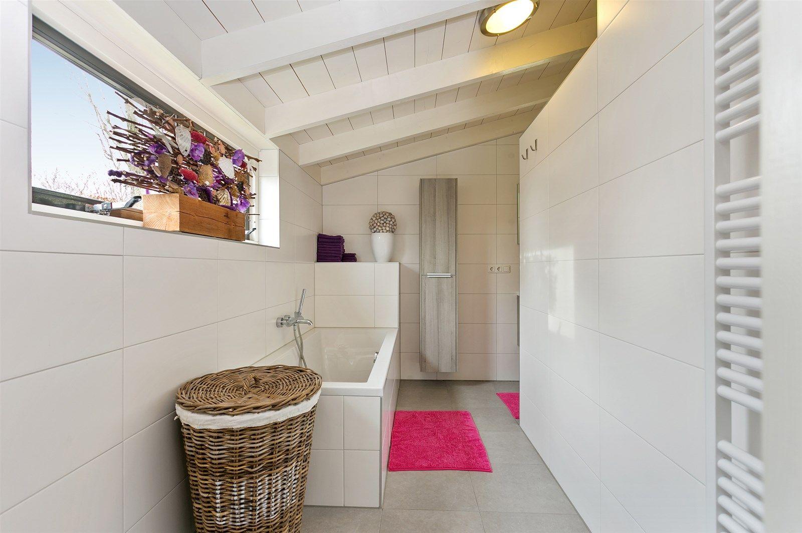Deze karaktervolle vrijstaande woning met vrijstaande schuur, tweetal opritten en multifunctionele ruimte welke nu is ingericht als showroom, ligt op een fraaie landelijke locatie nabij de bossen en het dorp. De woning is keurig afgewerkt en onder andere voorzien van een ruime woonkamer, een royale leefkeuken met kookeiland, een badkamer op de begane grond en een showroom met vide welke voor vele doeleinden geschikt is. De eerste verdieping is voorzien van drie slaapkamers en een moderne badkamer. Rondom de woning is een prachtige tuin aangelegd, welke bestaat uit een gazon, diverse terrassen, een veranda aan huis, berging, borders met planten en bomen en een dierenweide. De achtertuin is eveneens via een tweetal opritten te bereiken.  BESTEMMINGSPLAN De locatie is gelegen in het bestemmingsplan -buitengebied 1990—partiele herziening 1994- en heeft daarin de bestemming -Agrarisch gebied-.  -De agrarische bestemming is recent uitgebreid met een zaakgebonden overgangsrecht waardoor burgerwoning op deze locatie is toegestaan. Voor meer informatie neem contact op met ons kantoor. -   BEGANE GROND Hal/garderobe met toegang tot de achter entree, woonkamer en middels een vaste trap is de eerste verdieping bereikbaar.  Afwerking- Tegelvloer met vloerverwarming, houten wanden en een houten brikken plafond.  Achter entree met toegang tot de badkamer, keuken en toiletruimte. Afwerking- Tegelvloer met vloerverwarming, deels lambrisering met daarboven stucwerk wanden en een houten balken plafond.  Toiletruimte met zwevend toilet en fonteintje. Afwerking- Tegelvloer, wandtegels en een houten balken plafond.  Een moderne, luxe badkamer met ligbad, een inloopdouche (hand– en stortdouche), wastafelmeubel en een hygrostaat (automatische afzuiger met vochtsensor). Afwerking- Tegelvloer met vloerverwarming, wandtegels en een houten balken plafond.  Moderne open woonkeuken uitgerust met o.a. een kookeiland voorzien van een eiken werkblad, spoelbak, 2-pers vaatwasser, 6-pits gaskookplaat
