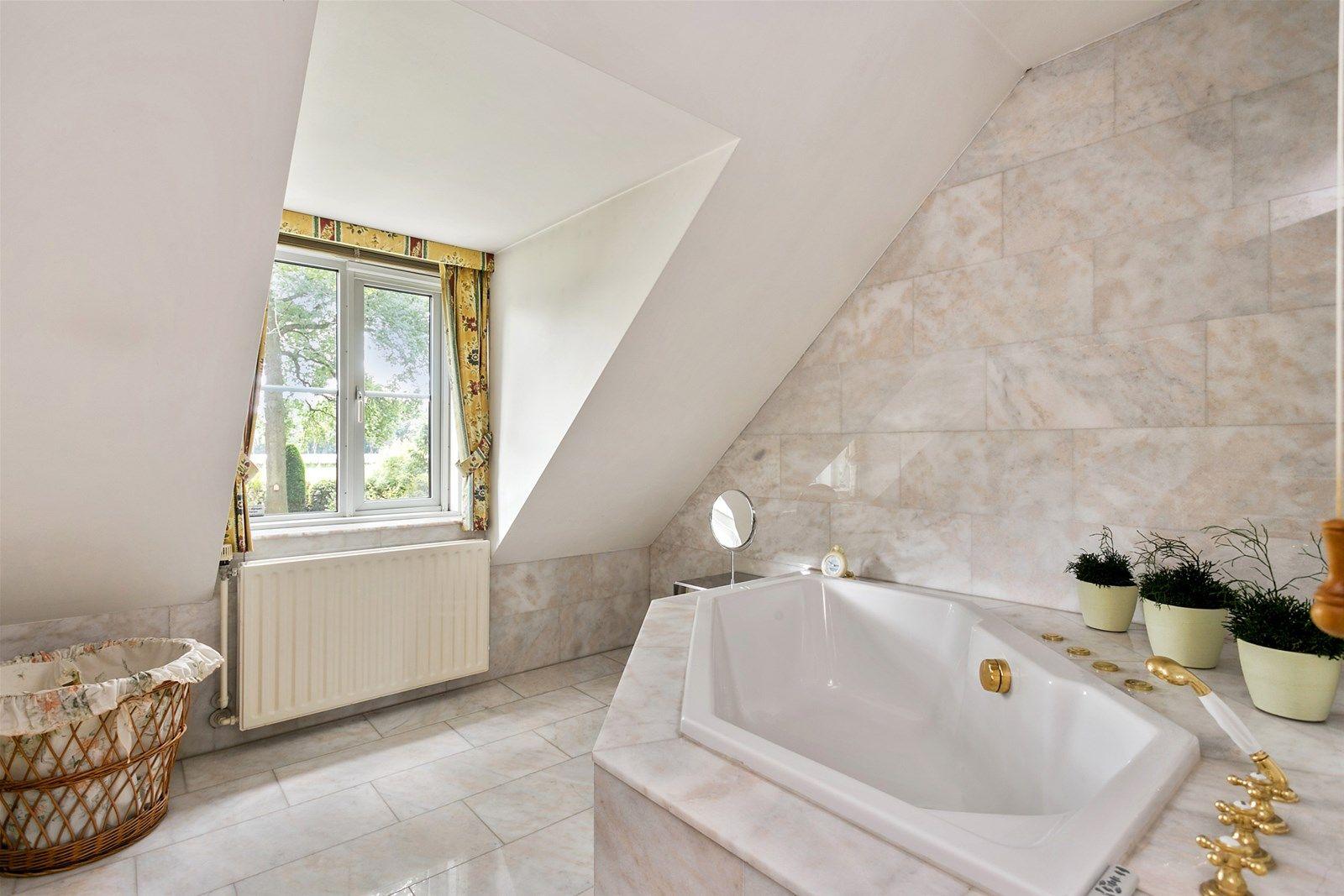 Deze karakteristieke woonboerderij is goed onderhouden en rustig gelegen in het buitengebied van Rijsbergen, op een ruim perceel van 5.135 m². Bij de woonboerderij behoren een vrijstaande garage met extra bergruimte, twee opritten en een schitterende parkachtige tuin met veel privacy.   De woning is o.a. voorzien van een riante woonkamer met openslaande tuindeuren, een royale woonkeuken, fraaie eetkamer met authentieke schouw, drie ruime slaapkamers, een luxe badkamer, doucheruimte en een multifunctionele kamer. In 1997 is er een aanbouw gerealiseerd voorzien van een eigen entree, woon-/slaapruimte en badkamer voor minder valide personen en is dan ook rolstoelvriendelijk. Deze ruimte is tevens uitstekend geschikt als kantoor- of praktijkruimte.  De ligging is ideaal. In het mooie buitengebied met rust en ruimte om u heen, maar ook binnen enkele minuten van de dorpskern van Rijsbergen met alle dagelijkse voorzieningen. Rijsbergen is gunstig gelegen tussen Rotterdam en Antwerpen en ligt nabij de plaatsen Zundert, Etten-Leur en Breda. In de omgeving zijn een tal van leuke voorzieningen te vinden. Zo kunt u een ijsje gaan eten bij de ijssalon, met de kinderen spelen in de binnen- en buitenspeeltuin of zwemmen in het binnenzwembad. Ook de jaarlijkse bloemencorso in Zundert is een topevenement dat erg leeft in de gemeente.  BEGANE GROND   Ruime entree/hal met vaste kast en meterkast die toegang biedt tot de ruime eetkamer. Afwerking- Plavuizenvloer, deels stucwerk wanden, deels structuurverf wanden en een balkenplafond.   Ruime eetkamer met schouw en haard en openslaande tuindeuren naar het terras. De grote ramen in de eetkamer geven een mooie lichtinval en bieden een fraai uitzicht over de prachtige tuin. In deze kamer bevindt zich tevens een mooie nis, dit is de voormalige schouw. Afwerking- Marmeren vloer, behangen wanden en een balkenplafond.   Hal met hardhouten bordestrap naar de eerste verdieping.  Afwerking- Marmeren vloer, behangen wanden en een balkenplafond.   