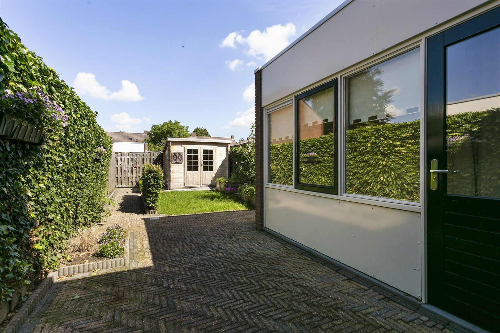 Deze instapklare tussenwoning met houten berging is gelegen in een rustige en kindvriendelijke woonstraat. De woning is fraai afgewerkt en onder andere voorzien van een ruime woonkamer, een open keuken, drie slaapkamers,  een praktische badkamer en zolderruimte. De voor- en achtertuin zijn beide verzorgd aangelegd. De achtertuin is voorzien van een houten berging en een achterom.   BEGANE GROND  Entree/hal met toegang tot de toiletruimte, woonkamer en vaste trap naar de eerste verdieping. Afwerking- Laminaatvloer, spachtelputz wanden en spachtelputz plafond. Meterkast- 7 groepen en 2 aardlekschakelaars.  Toiletruimte met toilet en fonteintje. Afwerking- Tegelvloer, wandtegels en spachtelputz plafond.  Zeer ruime woonkamer met vaste kast onder de trap, openslaande tuindeuren aan de achterzijde  naar de achtertuin en toegang tot de open keuken. Afwerking- Laminaatvloer, stucwerk wanden en stucwerk plafond.  Moderne woonkeuken uitgerust met een kunststof werkblad, spoelbak, inductiekookplaat, ingebouwde  afzuigkap, oven, koelkast en kastruimte. Er is een aansluiting voor een afwasmachine. Vanuit de keuken is de praktische bijkeuken bereikbaar. Afwerking- Laminaatvloer, wandtegels met daarboven stucwerk en stucwerk plafond.  Praktische bijkeuken met loopdeur naar de achtertuin.  Afwerking- Tegelvloer, spachtelputz wanden en agnes plafondplaten.  EERSTE VERDIEPING  Overloop met toegang tot drie slaapkamers, de badkamer en vaste trap naar de tweede verdieping. Afwerking- Laminaatvloer, stucwerk wanden en stucwerk plafond.  Slaapkamer 1- Een ruime slaapkamer aan de voorzijde van de woning. Afwerking- Laminaatvloer, structuurverf wanden en structuurverf plafond.  Slaapkamer 2- Een ruime slaapkamer aan de voorzijde van de woning. Afwerking- Laminaatvloer, structuurverf wanden en structuurverf plafond.  Slaapkamer 3- Een ruime slaapkamer aan de achterzijde van de woning. Afwerking- Laminaatvloer, structuurverf wanden en structuurverf plafond.  Praktische badkamer uitgerust me