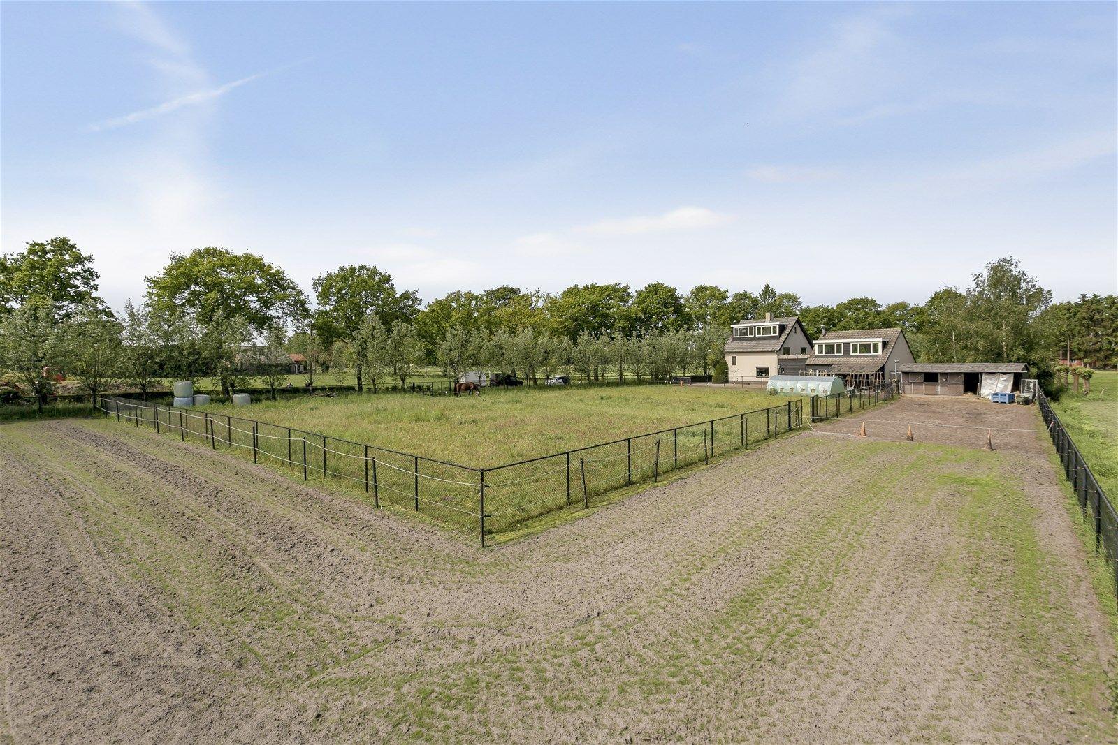 Op een prachtige - landelijke locatie gelegen uitgebouwde vrijstaande woning met dubbele paardenstal, berging/veranda/dierenverblijf en weiland wat uitermate geschikt is voor het hobbymatig houden van paarden/en of kleinvee.  Zowel aan de voor– als achterzijde van de woning heeft u een mooi uitzicht over de uitgestrekte landerijen. Wonen in alle rust, ruimte - privacy.  De begane grond heeft o.a. een ruime living, fraaie serre, praktische bijkeuken, leefkeuken en een multifunctionele ruimte die in gebruik kan worden genomen als kantoor-/speel/hobbykamer. De eerste verdieping heeft twee slaapkamers, een moderne badkamer en een ruimte in de aanbouw die nog naar eigen inzicht kan worden ingericht. Via een vaste trap bereik je de tweede verdieping waarbij de grote dakkapellen naast veel ruimte ook veel lichtinval creeren.  De tuin beschikt o.a. over een veranda, diverse terrassen, vijver en dierenverblijven waardoor u heerlijk kunt genieten van het buitenleven!  BEGANE GROND Voorentree/hal met toegang tot de leefkeuken en vaste trap naar de eerste verdieping.  Afwerking- laminaatvloer, Spachtelputz wanden en een stucwerk plafond.  Meterkast- 7 groepen en aardlekschakelaarbeveiliging.   Leefkeuken in hoekopstelling uitgerust met een houten aanrechtblad, dubbele spoelbak,  4 pits gas kookplaat, vaatwasser, combimagnetron en afzuigkap. De ruimte is voorzien van een wandkast en geeft toegang tot de kelder. Afwerking- laminaatvloer, stucwerk wanden en een stucwerk plafond.   Ruime living voorzien van schouw met houtkachel en dubbele deur naar de serre. Afwerking- laminaatvloer (met daaronder tegels), Spachtelputz wanden en een stucwerk plafond.   Fraaie serre met grote raampartijen en een tweetal schuifpuien. Afwerking- houten vloer en een houten plafond.  Portaal met toegang tot de volledig betegelde toiletruimte en bijkeuken. Afwerking- tegelvloer, stucwerk wanden en een stucwerk plafond.  Praktische bijkeuken met vaste kast, wasmachine aansluiting en opstelling van de cv 