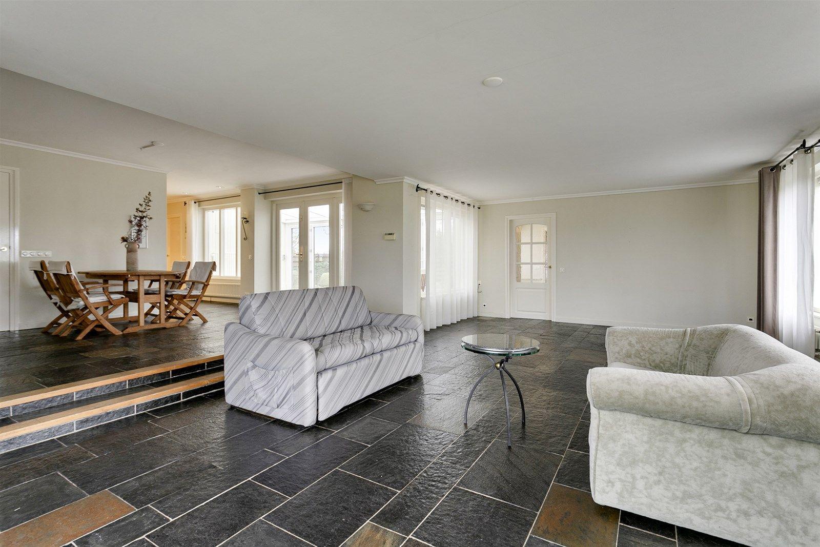 Deze riante semi- bungalow met inpandige garage, vrijstaande schuur en fraai aangelegde tuin is gelegen in een groenrijke omgeving op een mooie locatie in het buitengebied van Hoeven. Op korte afstand bereikt u natuurgebied -Pagnevaart- met schitterende wandel, fiets– en ruiterpaden en diverse uitvalswegen naar Etten-Leur, Breda, Roosendaal en Bergen op Zoom.   De begane grond heeft een zeer ruime living met erker, een open keuken, een serre en een praktische bijkeuken. De eerste verdieping heeft drie slaapkamers en een doucheruimte. Rondom de woning ligt een verzorgd aangelegde tuin waarbij u in alle rust - ruimte kunt genieten van het buitenleven!   BEGANE GROND Entree/hal met directe toegang tot de toilet, living, keuken en trapopgang naar de eerste verdieping.  Afwerking- Noorse leisteenvloer, spuitwerk wanden en een spuitwerk plafond.  Meterkast- 12 groepen, aardlekschakelaar en kookgroep.   Toiletruimte met -zwevend- closet en fonteintje.  Afwerking- tegelvloer, betegelde wanden en een spuitwerk plafond met spotverlichting.   Royale living waarbij het eetgedeelte zich op een hoger niveau bevindt. Via een openslaande deur  (3 delen) heeft u toegang tot de serre en middels een openslaande deur bereikt u de achtertuin.  Afwerking- Noorse leisteenvloer,, stucwerk wanden en een stucwerk plafond.   Open keuken uitgerust met een Italiaans hardstenen aanrechtblad, 1 ¼ spoelbak, keramische kookplaat, koelkast, vaatwasser, close-in boiler, apothekerskast en afzuigkap. De ruimte geeft toegang tot de  bijkeuken.  Afwerking- Noorse leisteenvloer, stucwerk wanden en een stucwerk plafond.   Praktische bijkeuken met stortbak en toegang tot de serre, keuken en garage.  Afwerking- tegelvloer, deels stucwerk en deels wit geverfde houten schroten wanden en plafond.   Fraaie serre met openslaande deuren (6 delen). Deze ruimte kan helemaal open en het behoort tevens tot de mogelijkheid om hier een veranda te realiseren.   Doorgang met vaste kast voorzien van opstelling van de cv co