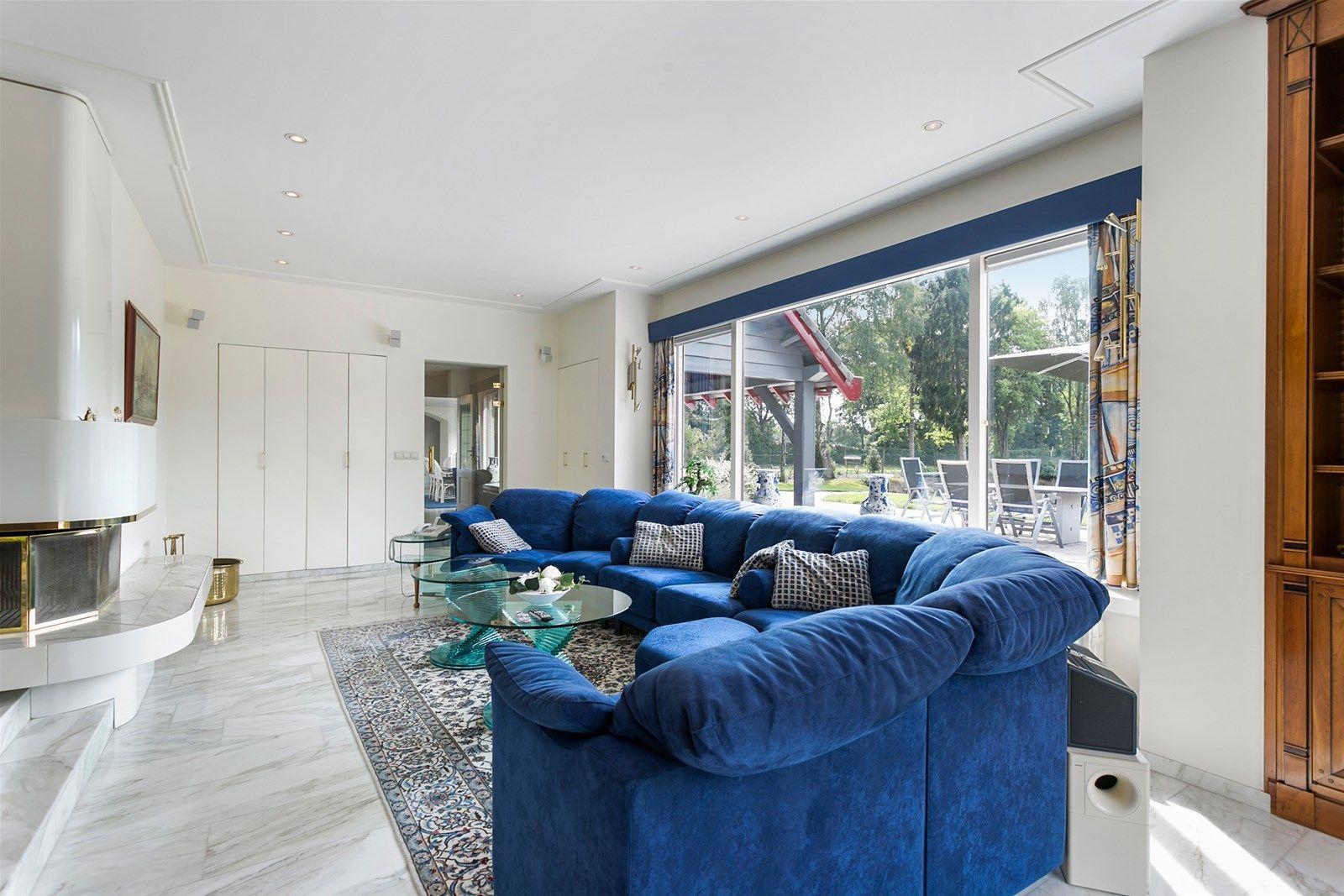 Voor mensen die op zoek zijn naar vrijheid, privacy en de schoonheid van het Brabantse landschap, bieden wij u dit imposante landhuis aan op totaal 90.110 m² grond. Dit volledig vrij gelegen landhuis is keurig onderhouden en luxe afgewerkt, waarbij is nagedacht over het optimaliseren van het comfortniveau. Het landhuis is uitermate geschikt om wonen en werken te combineren. Het beschikt over een inpandig bereikbare dubbele garage met daarboven een luxueus ingericht appartement met kantoorruimte welke ook te gebruiken is als gastenverblijf/aanleunwoning. Op het perceel bevinden zich diverse bijgebouwen, waaronder een voormalig zwembadhuis, stal,tuinhuis/opslag, werktuigenberging, kippenren en meerdere schuilhokken in de diverse dierenweides.  Het terrein is geheel omheind en voorzien van naald- en loofbossen, een fraaie vijverpartij met steiger, een golf green en het is toegankelijk middels een tweetal oprijlanen met op afstand bedienbare elektrische poorten met intercom en camera.  BEGANE GROND WOONHUIS Via de overdekte entree bereikt men de voorentree. Deze ruimte biedt middels fraaie dubbele deuren toegang tot de hal en toiletruimte en via de trapopgang is de eerste verdieping te bereiken. Afwerking- Vloerbedekking, stucwerk wanden en een stucwerk plafond met spotverlichting.   Meterkast- 17 groepen en aardlekschakelaarbeveiliging.   Toiletruimte met een -zwevend- closet en wastafelmeubel. Afwerking- Tegelvloer, betegelde wanden en een MDF plafond met spotverlichting.   Ruime hal voorzien van een garderobekast, wandkast en een bedieningspaneel voor een drietal poorten en een toegangs– en camera controle voor de hoofdpoort.. De ruimte biedt toegang tot de eetkamer, woonkamer en heeft openslaande deuren naar de achtertuin. Afwerking- Marmeren vloer met vloerverwarming, stucwerk wanden en een stucwerk plafond met  spotverlichting.   Mooie U-vormige woonkamer met niveau/hoogteverschil. De ruimte is voorzien van een open haard, een schuifpui naar het overdekt terras, e